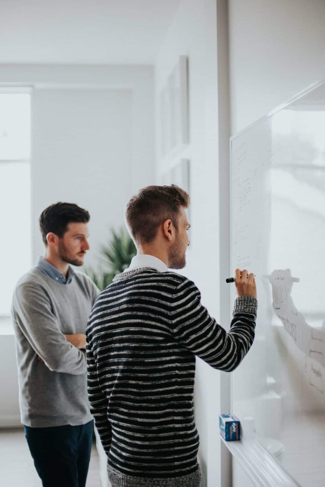 2 teammates writing a digital marketing strategy on a whiteboard